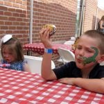 Photo of 2 children with painted faces at Teddy Bear Picnic