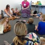 Photo of children, parents, and storyteller at Teddy Bear Picnic event