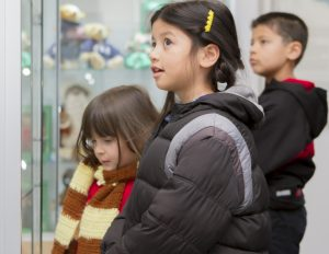 Three children looking into a museum display case