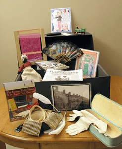 Photo of contents of the museum's educational Touch Trunk, including a cloth doll, a hand fan, white gloves, and a writing quill.